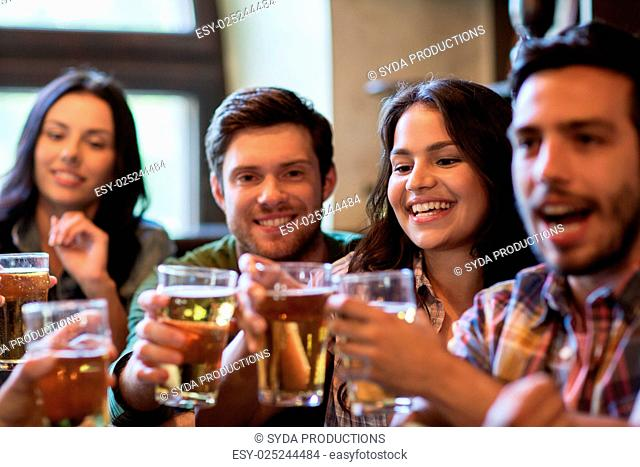 people, leisure, friendship and communication concept - happy friends drinking beer, talking and clinking glasses at bar or pub