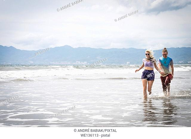 Beach scene with young woman and man running, Riviera Nayarit, Pacific Coast, Mexico