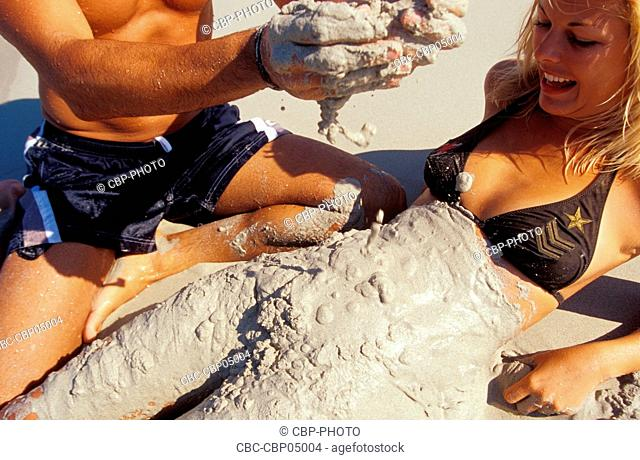 Young Couple at the Beach, Man Putting Wet Sand on Woman