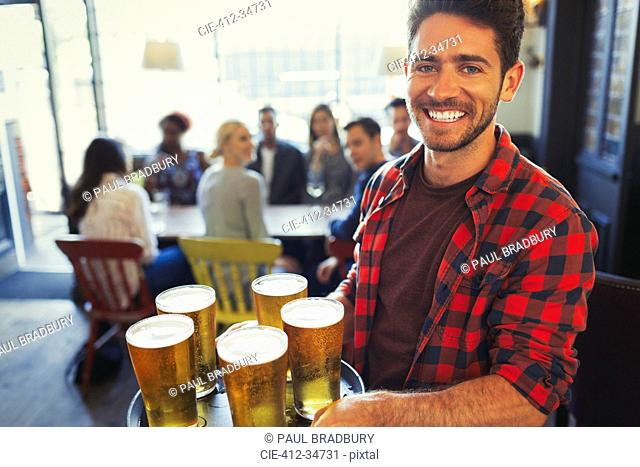 Portrait smiling bartender carrying tray of beer glasses in bar