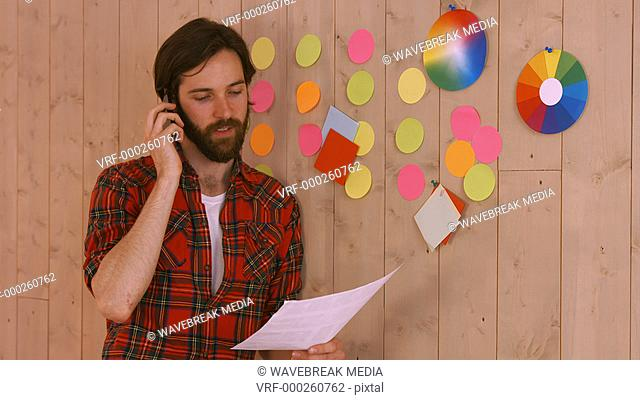 Casual hipster designer on the phone