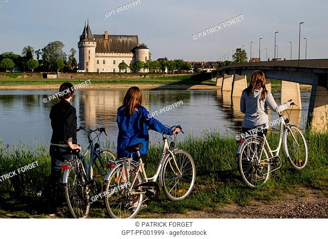 YOUNG WOMEN CYCLING ALONG THE 'LOIRE A VELO' CYCLING ITINERARY IN FRONT OF THE CHATEAU OF SULLY-SUR-LOIRE, SAINT-PERE-SUR-LOIRE, LOIRET 45, FRANCE