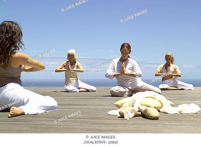 Group of women practicing yoga on boardwalk