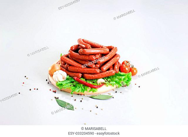 A composition of different sorts of sausages on the wood board with fresh vegetable