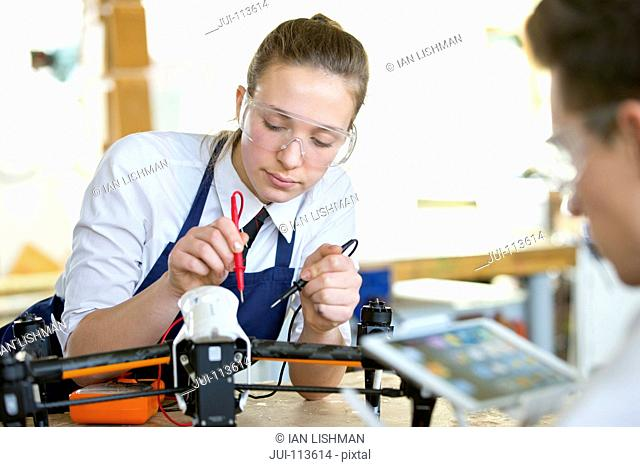 High school student using soldering iron assembling electronics in shop class