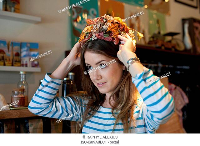 Young woman trying on floral hat in vintage shop