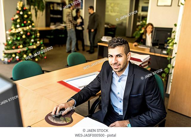 Portrait of smiling man working at desk in office with Christmas tree in background