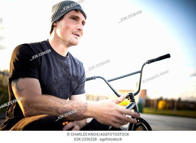 Portrait of bmxer in skate park sitting on bike