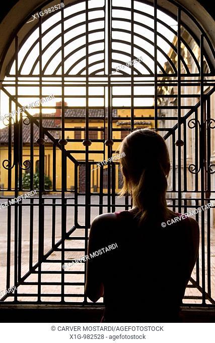 Woman staring out of iron window at the Iglesia de la Merced, Granada, Nicaragua