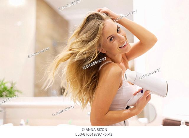 Natural blonde woman drying hair in bathroom. Debica, Poland