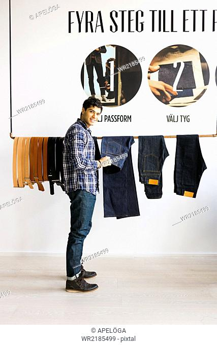 Side view portrait of young man choosing jeans in factory