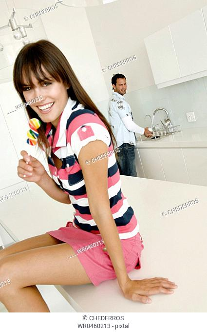Portrait of a young woman sitting on a kitchen counter and holding a lollipop