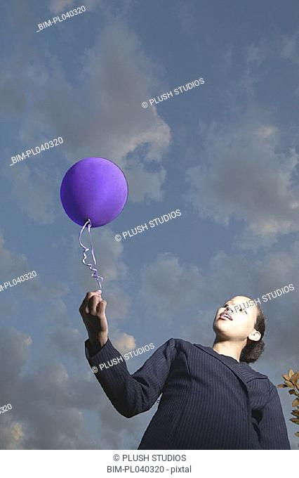 Low angle view of businesswoman with balloon