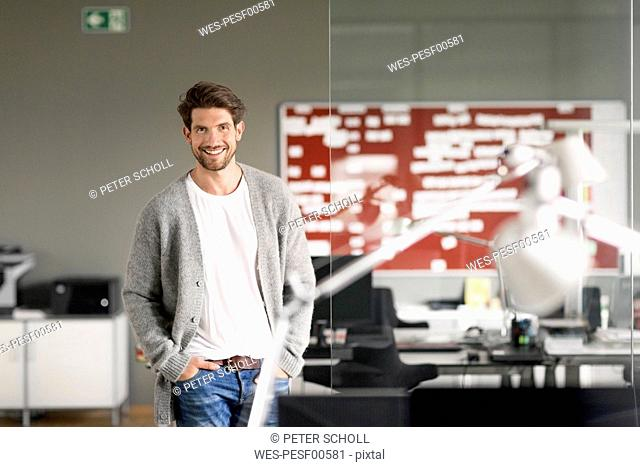 Dynamic businessman standing in office, smiling