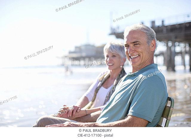 Portrait of senior couple relaxing on sunny beach