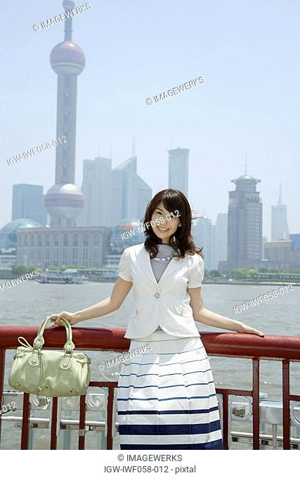 Young woman holding shoulder bag, smiling, portrait