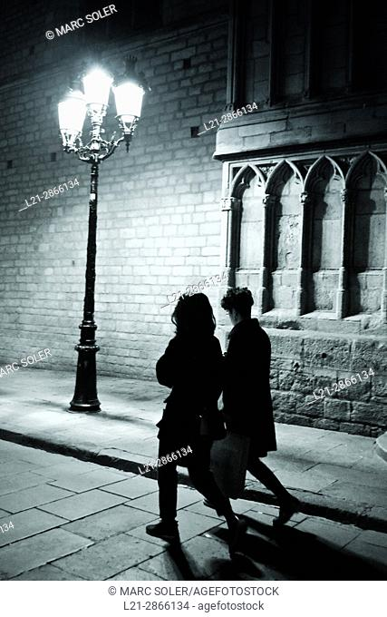 Silhouette of two women walking near wall of Santa Maria del Mar church at night. Barcelona, Catalonia, Spain