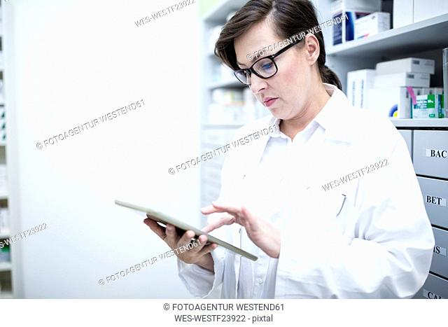 Pharmacist using tablet in pharmacy