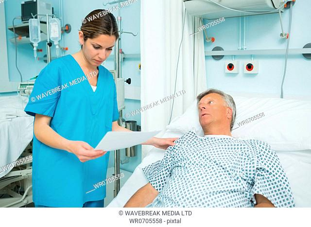 Nurse talking to a patient lying on a bed while holding a paper in a hospital
