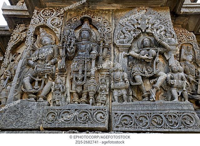 Ornate wall panel reliefs depicting (from left) Deity playing damaru, Vishnu and dancing Sarswati, Hoysaleshwara temple, Halebidu, Karnataka, india
