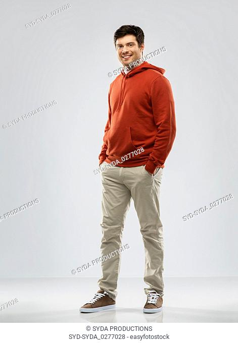 young man in red hoodie over grey background
