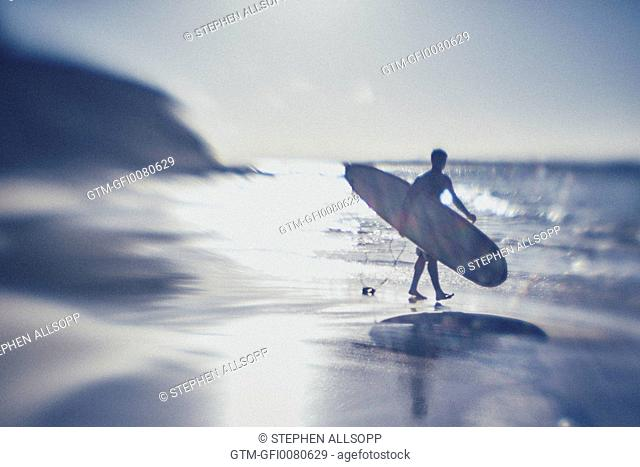 Silhouetted male carrying a surfboard walking along an otherwise deserted beach