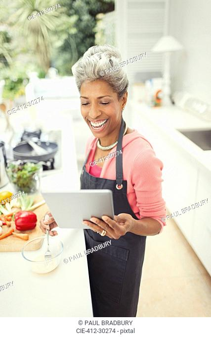 Smiling mature woman with digital tablet cooking in kitchen