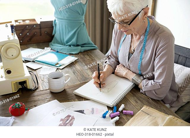 Senior woman seamstress sketching in notebook in home office