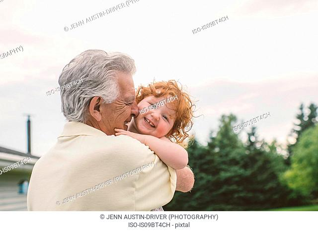 Female toddler with curly red hair in grandfather's arms, portrait