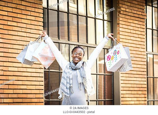 Portrait of woman holding her shopping bags above head, Johannesburg, South Africa