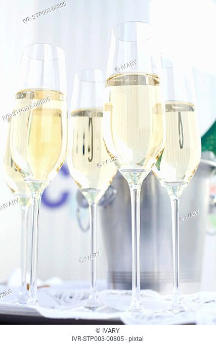 Close-up of white wine glasses with bottle in bucket in background