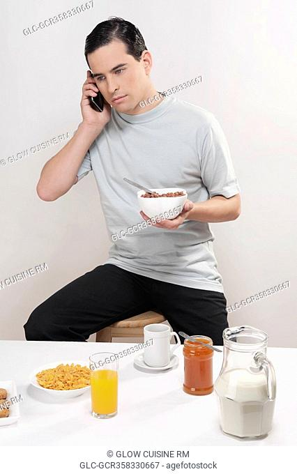 Man talking on a mobile phone at breakfast
