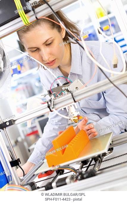 Student using a 3 dimensional (3d) printer