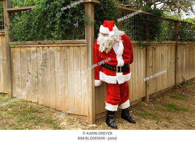 Santa hiding behind fence