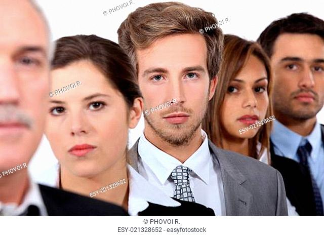 Closeup of the faces of a group of serious young executives and their older boss
