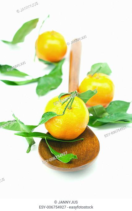 mandarin with green leaves on a wooden spoon isolated on white