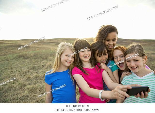 Schoolgirls taking self-portrait through smart phone during field trip