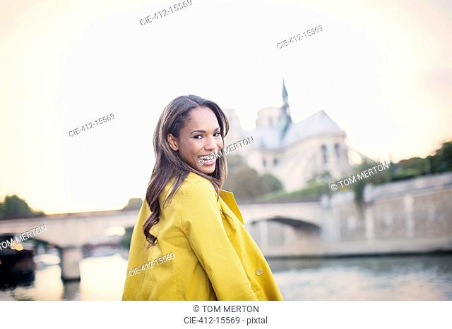 Woman smiling along Seine River near Notre Dame Cathedral, Paris, France