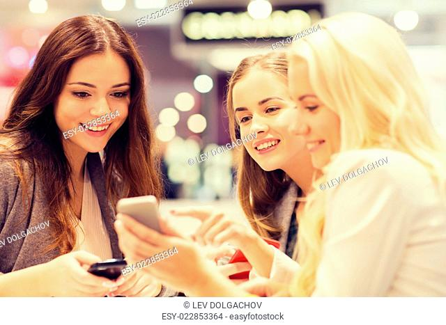 sale, consumerism, technology and people concept - happy young women with smartphones and tablet pc in mall or city