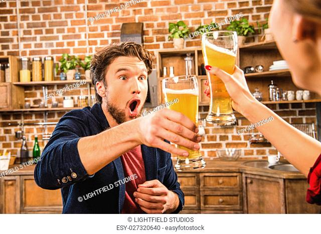 Happy man toasting with beer at home party