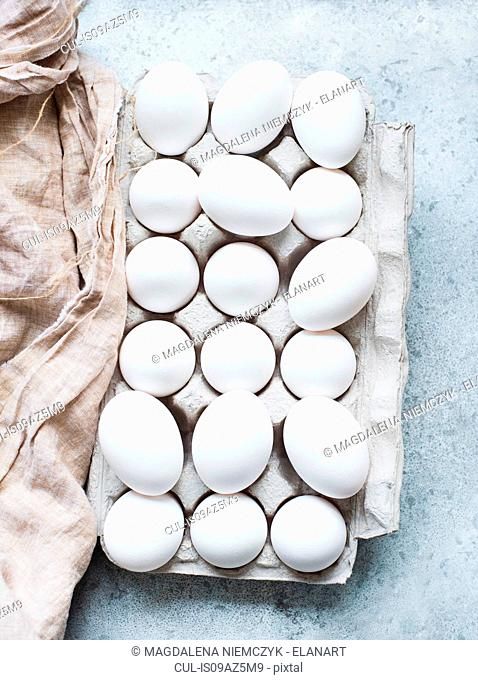 Overhead view of white eggs in carton