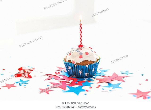 independence day, celebration, patriotism and holidays concept - close up of glazed cupcake or muffin with burning candle and stars cofetti decoration on table...