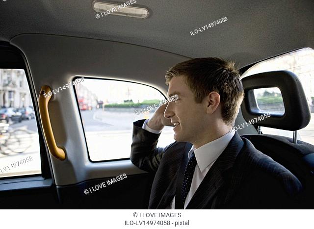 A businessman in a taxi, talking on his mobile phone