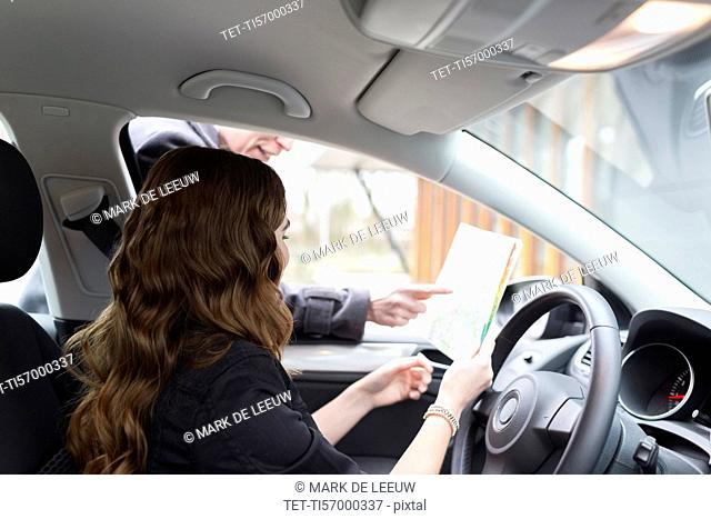 Man giving directions to young woman in car