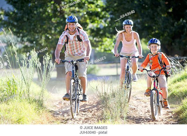 Family mountain biking on country track