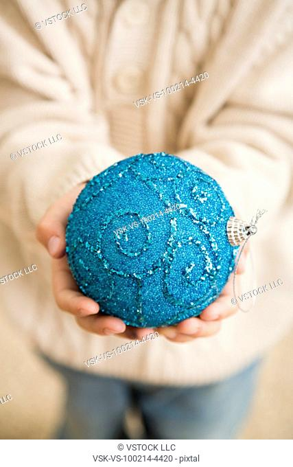 Hands of boy (6-7) holding blue bauble
