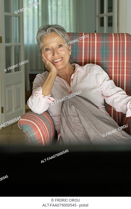 Smiling senior woman sitting in armchair