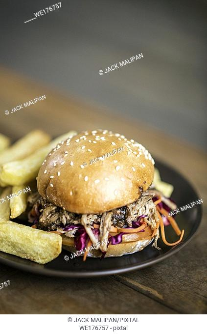 pulled pork and coleslaw salad burger sandwich with french fries snack meal