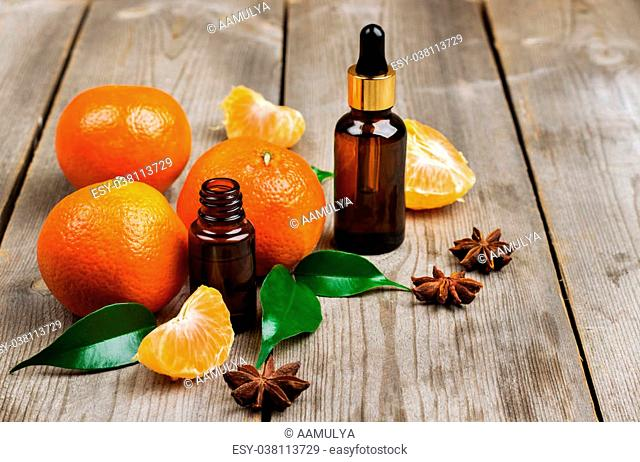 Still life, food and drink, healthcare, beauty concept. Organic tangerine essential oil on a rustic wooden table. Selective focus