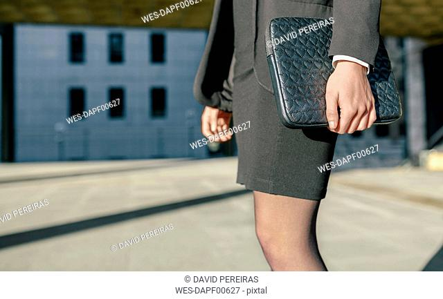 Businesswoman carrying briefcase, mid section